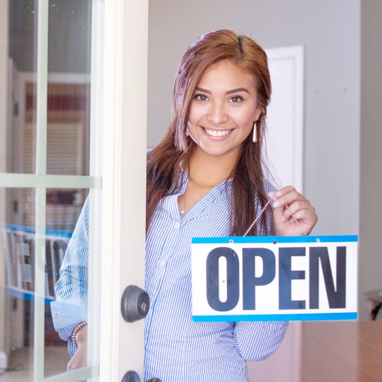 Woman opening her store with an open sign